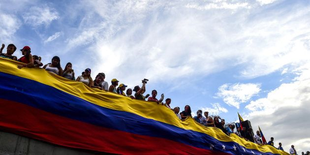 Opposition activists hold a large Venezuelan flag during a protest in Caracas, on July 24,
