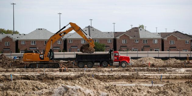 Construction workers build homes on a lot in Vaughan, a suburb with an active real estate market, in...