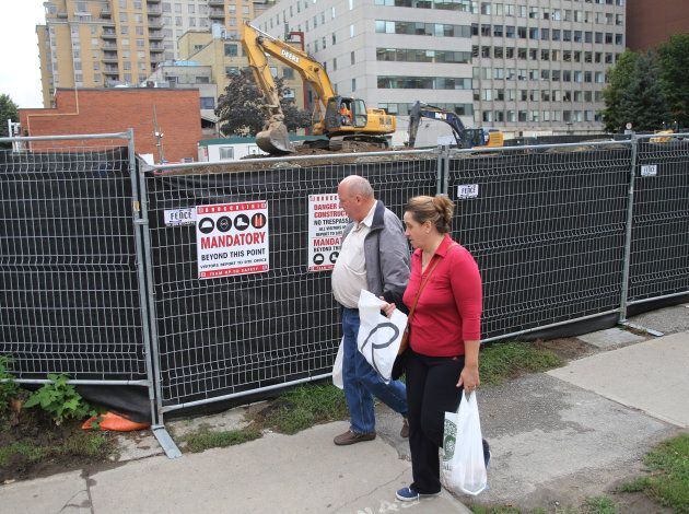 A couple pass a condominium construction site on what used to be a neighbourhood of single family homes...