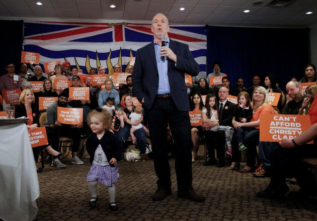 A young girl walks in front of British Columbia's New Democratic Party leader John Horgan while he addresses supporters during a campaign stop at a hotel in Surrey, B.C., May 8, 2017.