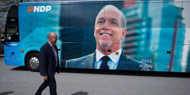 B.C. NDP Leader John Horgan walks to speak to reporters while bringing voters to a polling station to...