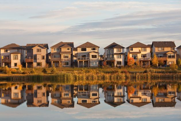 A row of houses reflected in a pond in Calgary, Alta. Calgary is one of six major cities to see an improvement...