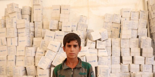 Rayan stands in the tent for new arrivals at Salamiyah camp. The UNICEF boxes behind him are UNICEF's...