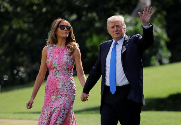 U.S. President Donald Trump waves as he and First Lady Melania Trump depart from the White House on route...