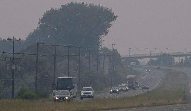 Cars and trucks drive though the thick smoke caused by wildfires just outside of Kamloops, B.C., on July...