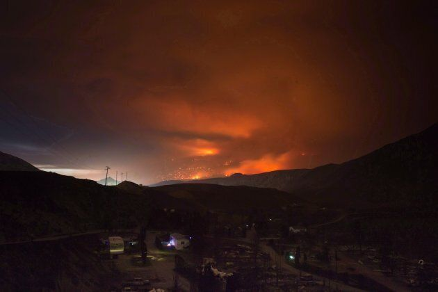 A wildfire burns on a mountain in the distance east of Cache Creek behind a trailer park that was almost...