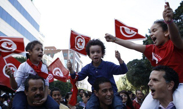 Protesters wave flags and shout slogans during a demonstration in Tunis March 20, 2012. Thousands of...