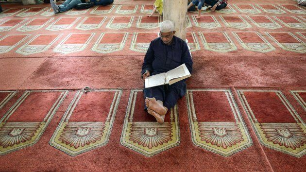 An Egyptian worshipper reads from the Koran, Islam's holy book, inside the 10th century historic al-Azhar...
