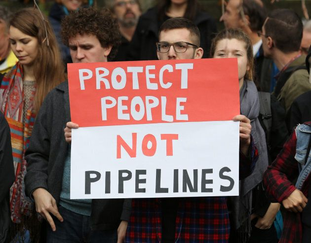 Protesters hold a rally at City Hall before a march against the proposed expansion of Kinder Morgan's...