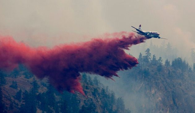 A water bomber drops a load of fire retardant on a forest fire burning on the edge of Kelowna, B.C. at...
