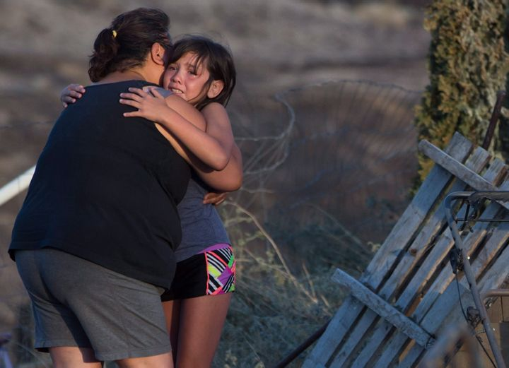Nevaeh Porter, 8, is comforted by her grandmother Angie Thorne as they view the remains of their home that was destroyed by wildfire on the Ashcroft First Nation, near Ashcroft, B.C., late Sunday July 9, 2017.