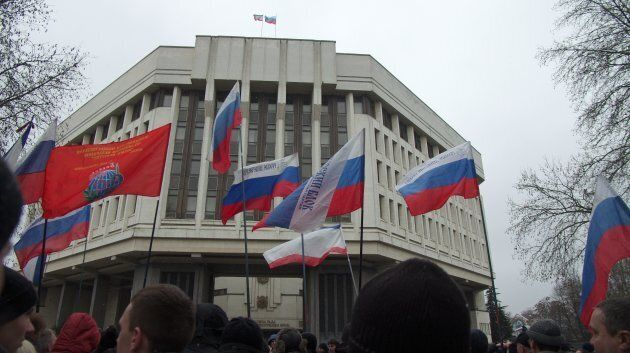Pro-Russian protesters hold Russian flags as they rally in front of the Crimean parliament in Simferopol...