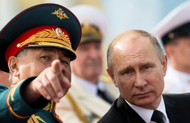 Russian President Vladimir Putin listens to Defence Minister Sergei Shoigu as they attend the Navy Day...