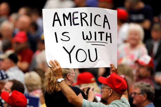 A supporter holds a sign during a rally with President Donald Trump at the U.S. Cellular Center in Cedar...