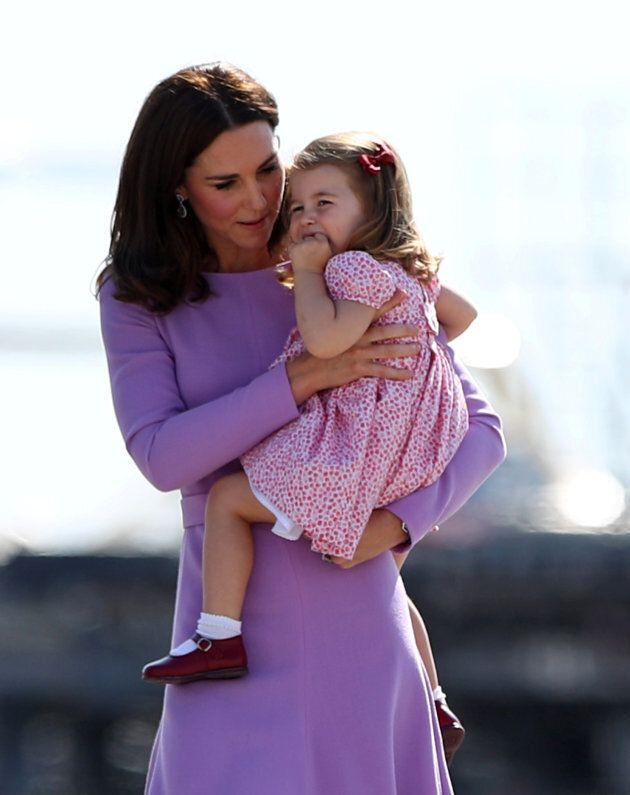 Princess Catherine, the Duchess of Cambridge holds Princess Charlotte before boarding their plane in...
