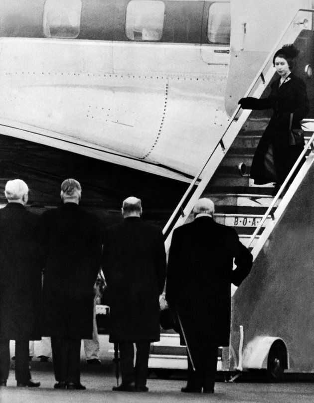 Queen Elizabeth II of England gets off plane, greeted by (from R to L) Sir Winston Churchill, Clement Attlee, Anthony Eden and Frederick James Marquis, 1st Earl of Woolton and Lord President of the Council, 08 February 1952, as she returns from Kenya. Queen Elizabeth II was proclaimed Sovereign of each of the Commonwealth Realms on 06 February 1952, after the death of her father King George VI in the night between 05 February and 06 February 1952. Princess Elizabeth heard the news of her father's death while staying at Treetops, a Game Lodge, in Kenya. (OFF/AFP/Getty Images)