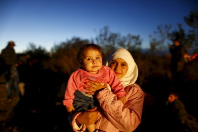 A Syrian migrant holds a baby as migrants rest while making their way towards the Greek border, on a...