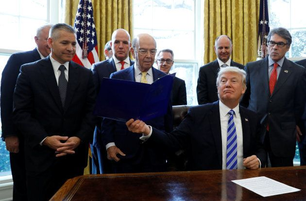 U.S. President Donald Trump smiles after announcing a permit for TransCanada Corp's Keystone XL oil pipeline while TransCanada Chief Executive Officer Russell Girling (L), U.S. Commerce Secretary Wilbur Ross (C) and U.S. Energy Secretary Rick Perry (R) stand beside him in the Oval Office of the White House in Washington, U.S., March 24, 2017.