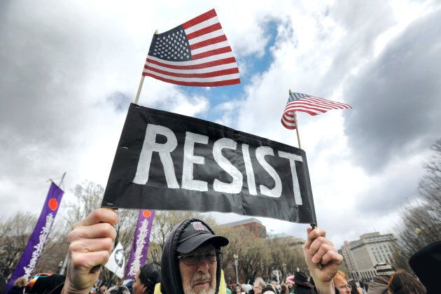 """A protester holds a """"resist"""" sign as Indigenous activists and supporters hold a protest march and rally in opposition to the Dakota Access and Keystone XL pipelines in Washington, D.C., March 10, 2017."""