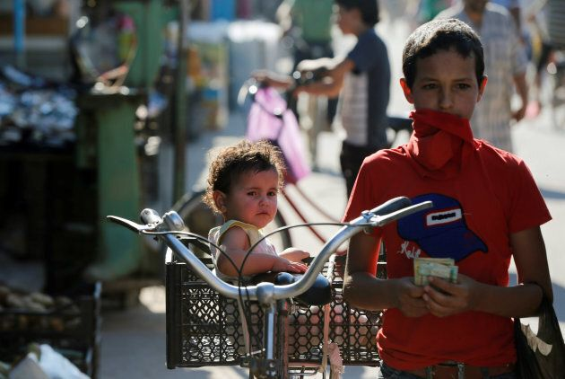 A Syrian child sits in a basket on a bicycle at the main market during the Muslim fasting month of Ramadan at the Al-Zaatari refugee camp in Mafraq, Jordan, near the border with Syria June 1, 2017.