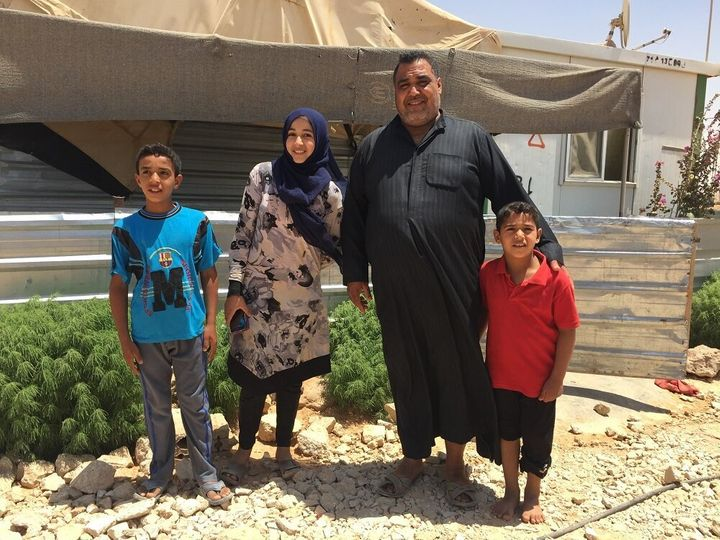Abu Kareem with three of his four children outside their home in Za'atari refugee camp.