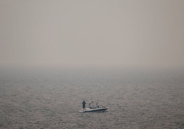 Thick smoke from wildfires fills the air as a man stands on a boat while fishing on Kamloops Lake west...