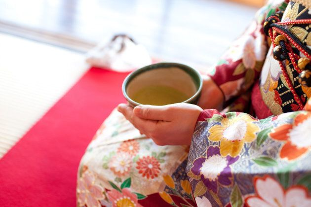 A woman in a Japanese kimono drinking a cup of green