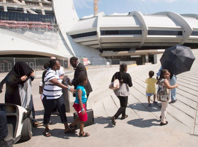 A group of asylum seekers leave Olympic Stadium to go for a walk, in Montreal on