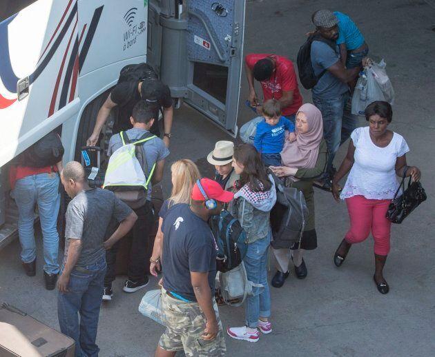 Asylum seekers take their belongings as they arrive at Olympic Stadium, in Montreal on