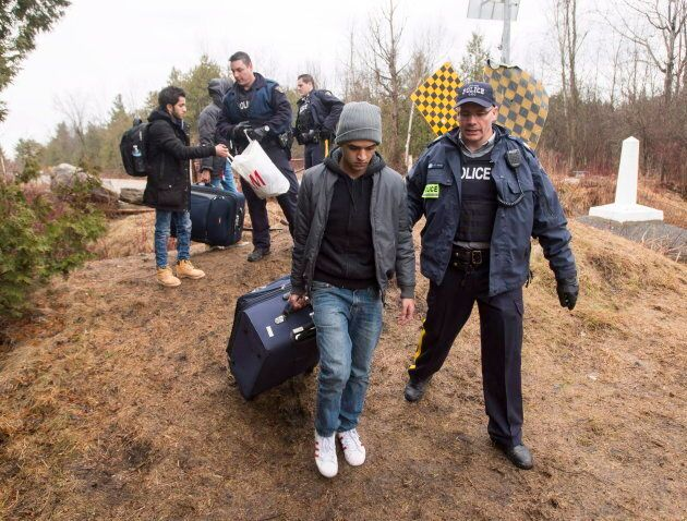 Asylum seekers, claiming to be from Yemen, are arrested by RCMP officers after crossing the border from...