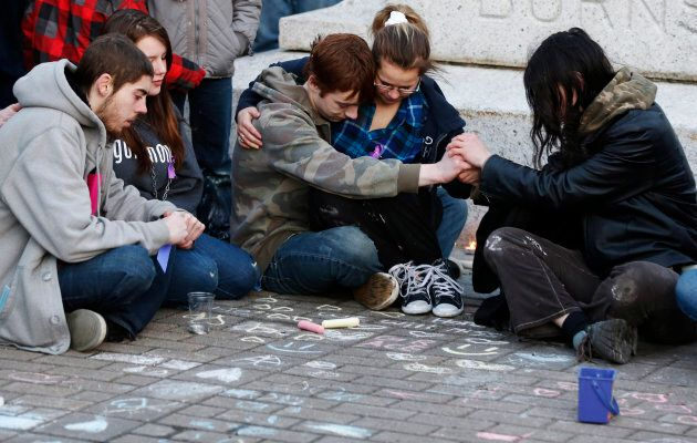 A group of teens comfort each other during a vigil for 17-year-old Rehtaeh Parsons at Victoria Park in...
