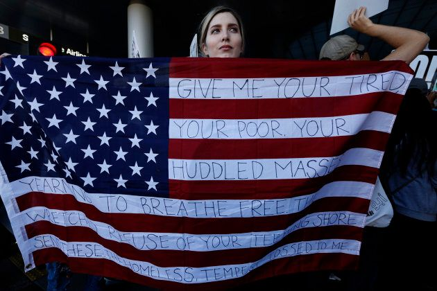 Chella, from Sherman Oaks, holds the U.S. flag with words from the sonnet, 'The New Colossus,' by poet...