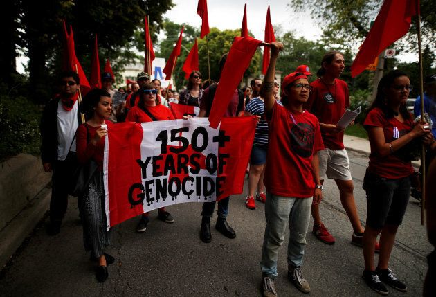"Indigenous rights activists hold a sign reading ""150 + Years of Genocide"", as they march following the ""Unsettle Canada Day 150 Picnic"", as the country marks its 150th anniversary with ""Canada 150"" celebrations, in Toronto, Ont., July 1, 2017."
