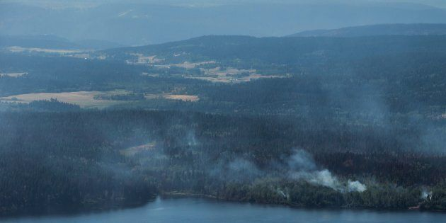 Wildfires are seen from a Canadian Forces Chinook helicopter as Prime Minister Justin Trudeau views areas...