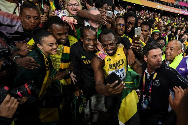 Usain Bolt of Jamaica celebrates during a lap of honour following finishing in third place in the mens...