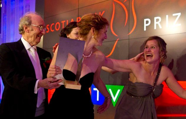 Founder Jack Rabinovitch holds the trophy as Johanna Skibsrud, receives a hug from her sister Kristin Skibsrud Ross (right) in November of 2010. (PHOTO: David Cooper/Toronto Star via Getty Images)