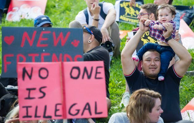 A man holds up a baby during a rally in support of asylum seekers outside the Olympic Stadium in Montreal,...