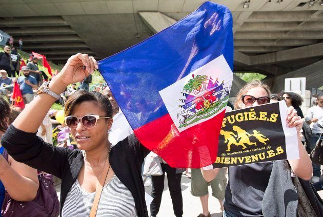 A woman holds up a Haitian flag in support of asylum seekers during a rally outside the Olympic Stadium...
