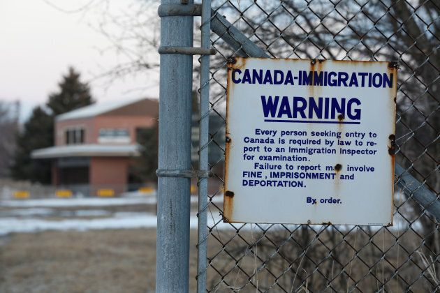 A sign is seen on a fence on the U.S. side of the former Canada-U.S. border crossing in Noyes, Minnesota,...