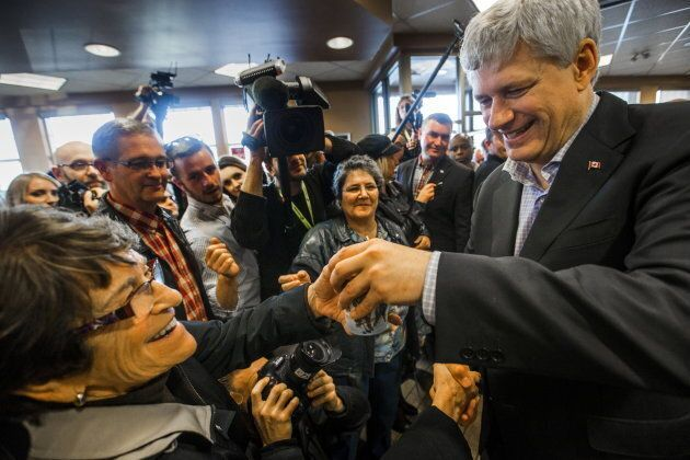 Stephen Harper hands out coffee at a Tim Horton's restaurant in Fredericton, N.B. on Oct. 16,