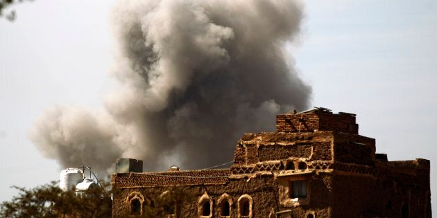 Smoke billows behind a building following a reported air strike by the Saudi-led coalition in the Yemeni...