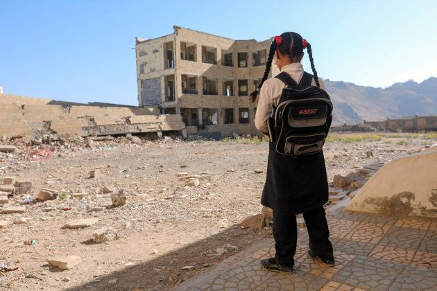 A Yemeni school girl stands outside a school on March 16, 2017, that was damage in an air strike in the...
