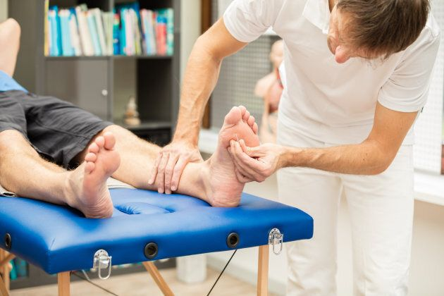 A doctor, testing the sensibility of a patient's foot. This test is often used for checking neuropathy...