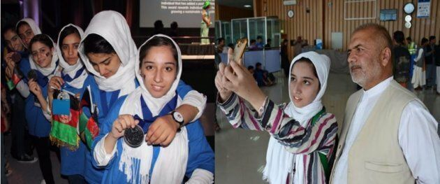 Afghan teenager Fatemah Qaderyan takes a photograph with her father at Herat International Airport on...
