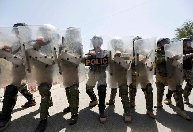 Afghan civil order policemen take position as Afghanistan's Hazara minority attend a protest in Kabul,...
