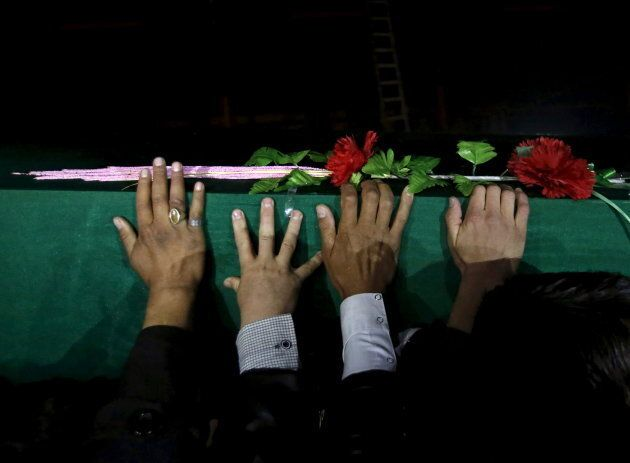 Men carry one of the coffins for the seven people who were killed by unknown militants, during a protest...