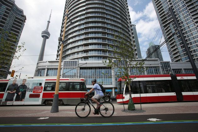 A cyclist uses the newly opened bike lanes on Queens Quay between Yonge and Bathurst on June 18,