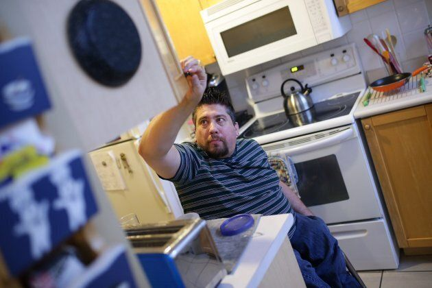 Teaching assistant Ryan Leoworthy rolls around his kitchen at his Mississauga condo on December 18, 2015. Leoworthy suffers from Spinal Bifida, limiting his mobility and the constant strain on his upper body makes it incredibly difficult to go about his daily life.