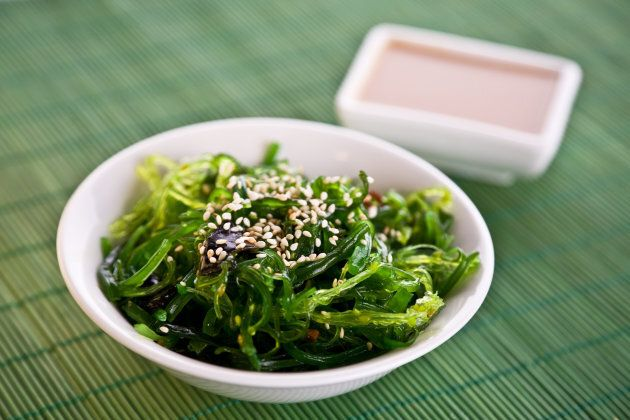 Wakame seaweed salad with nut sauce, garnished with sesame seeds and red chili pepper.