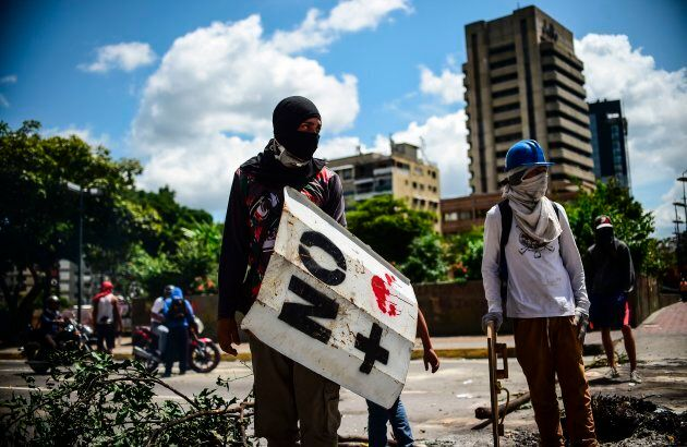 Anti-government activists demonstrate against Venezuelan President Nicolas Maduro at a barricade set...